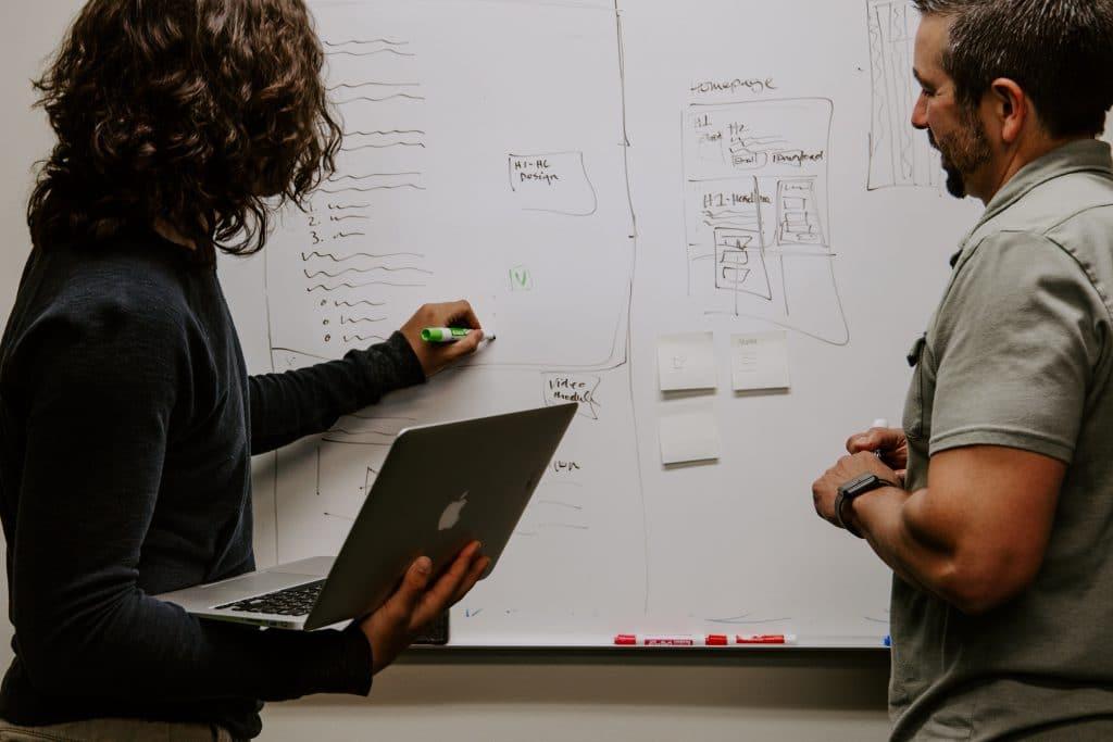 2 personnes travaillent au tableau blanc